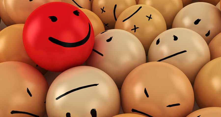 Stock photo of yellow and red balls with different expressions drawn on them - happy, sad, angry