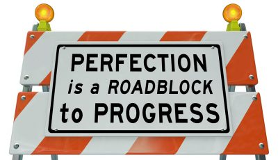 Hazard road sign: Perfection is a roadblock to progress