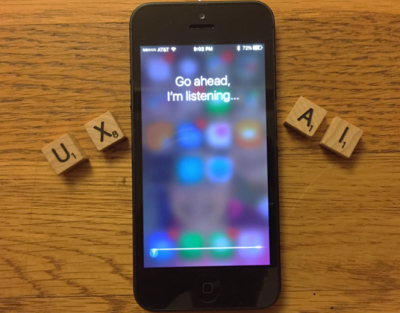 iPhone with words on screen: Go ahead, I'm listening. Surrounded by scrabble letters UX and AI