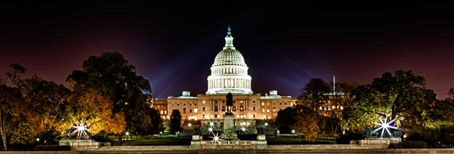 A photo of the US Capitol lit up at night.