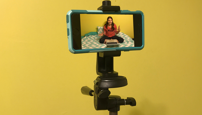 A teen girl is pictured in an iPhone that is mounted on a tripod. She is talking about something on her laptop screen.