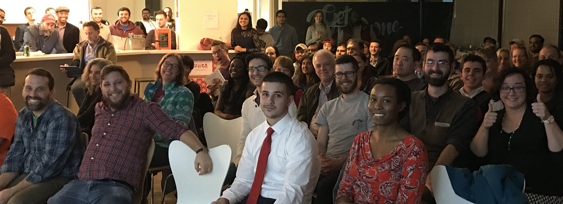 Many attendees at an event all looking at the camera and smiling