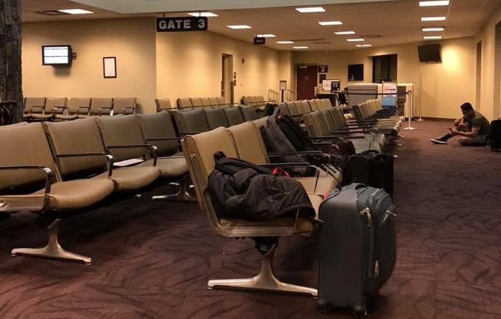 Empty seats at an airport gate with a person sitting on the floor working