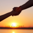 "Two clasped hands supporting each other against a sunset in the background with text ""UX for Good"""