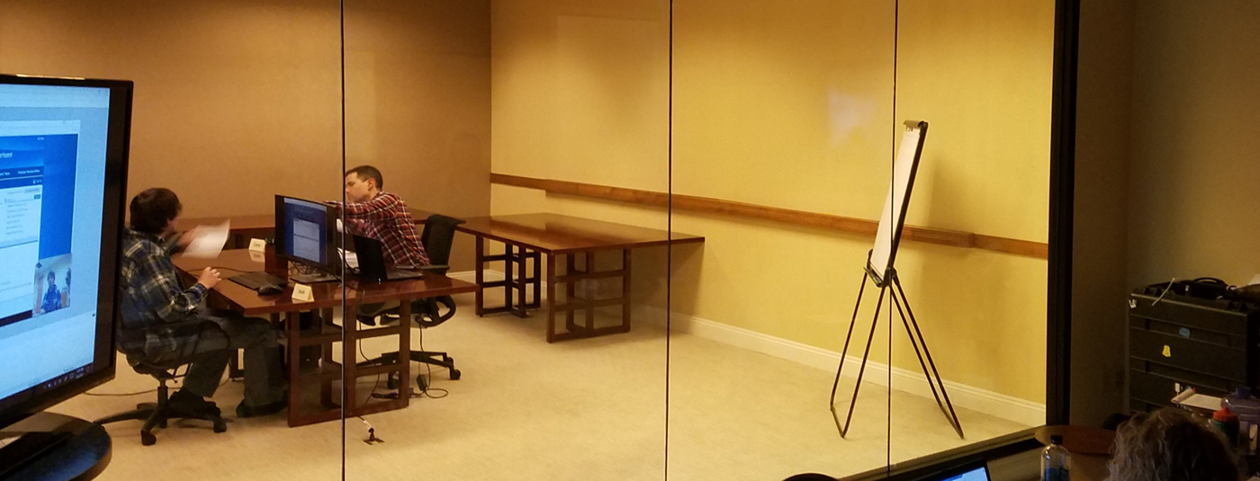 Cory moderating a usability study with a participant while observers watch from a back room