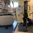 Home gym with Oculus Quest 2 VR in the foreground and the Adaptive Motion Trainer and exercise equipment in the background